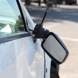 Damaged car and broken side rear view mirror. Vertical composition.